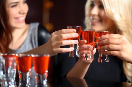 tomando alcohol: Amistad por siempre. Selectivo se centran en tres disparos con bebida de color rojo y sonrientes ni�as en los vidrios que sostienen borrosas