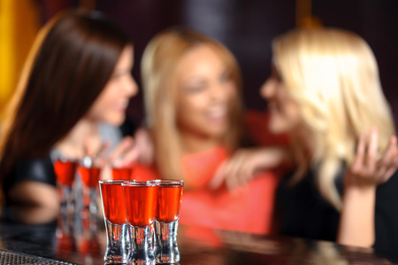 Night life. Selective focus on three shots on the bar counter and three girls in blurry