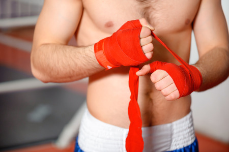 binding: Boxing bandage. Close up of a sportsman binding red boxing bandage in a gym