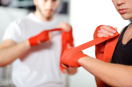 boxing sport: Get prepared to the fight. Athletic guys pulling on hands red boxing bandages