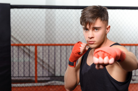 opponent: Handsome kickboxer. Young sportsman standing in a fighting cage is about to give a punch to his opponent Stock Photo