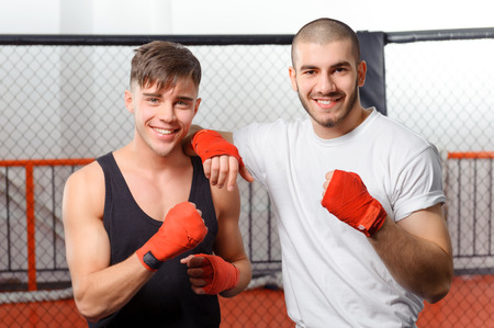Friendship. Two young handsome sportsmen smiling at the camera and standing in a fighting case with their hands in bandages