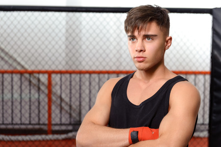 Fighter. Portrait of a young boxer standing in a fighting cage in a gym