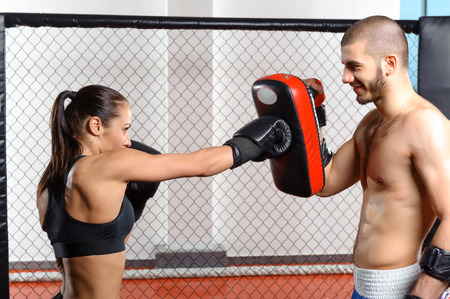 Sparring fight. Female mixed martial art fighter training with a couch in fighting cage Stock Photo