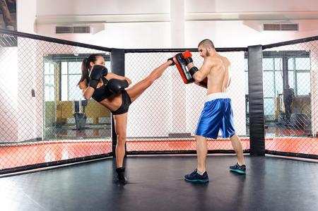 patada: Cuadro femenino. Sesión de entrenamiento de una mujer combatiente patear una almohadilla de perforación en manos de un sofá