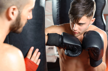 Getting stronger. Close-up of a young fighter kicking a punching bag with boxing gloves
