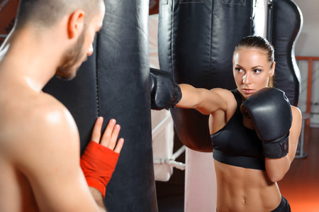 Strong jab. Young beautiful woman boxer kicking a punching bag with a jab