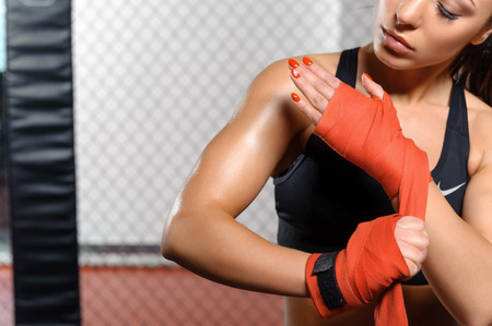 cruel: Cruel beauty. Female boxer binding boxing gloves and preparing for training Stock Photo