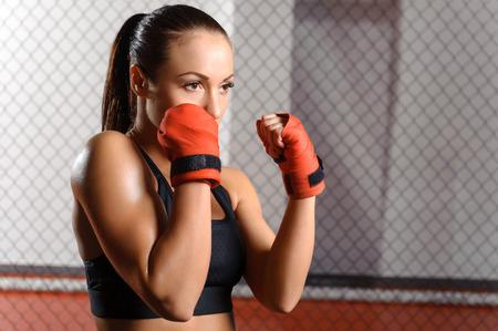 patada: Luchador profesional. Mujer hermosa joven en el boxeo rojo venda listo para luchar oponente en un ring de boxeo