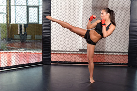 female boxing: High kick. Strong sportswoman shows her high kick in a boxing ring
