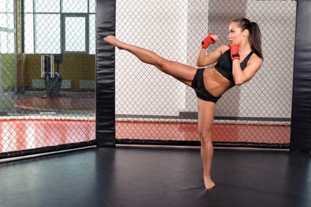 combate: Patada alta. Fuerte deportista muestra su alta patada en un ring de boxeo Foto de archivo