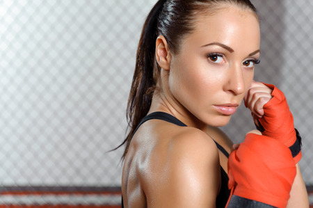 female boxing: Strong fighter. Young beautiful female boxer ready to fight an opponent