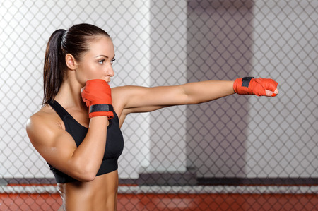 female boxing: Jab. Young strong and fit woman training her jab in a fighting cage Stock Photo