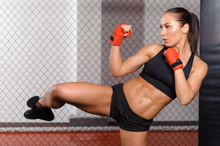 female kick: Low kick. Young beautiful female kickboxer showing her low kick Stock Photo