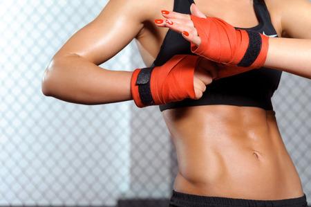 fighting: Huelgas de belleza. Primer plano de una mujer haciendo vendas de boxeo en una jaula de lucha Foto de archivo