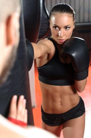 jab: Strong jab. Young beautiful woman boxer kicking a punching bag with a jab