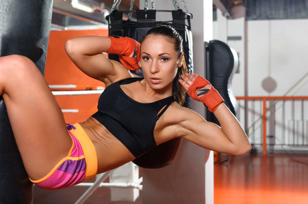Iron abs. Young beautiful sportswoman working at her abs hanging on a punching bag Stock Photo