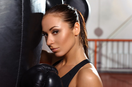 Passionate boxer. Close-up of a young attractive female boxer in boxing gloves leaning upon punching bag