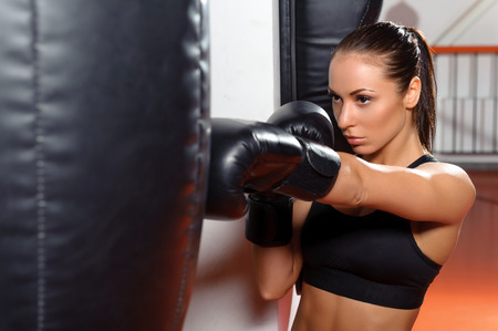 jab: Strong jab. Close-up of a young beautiful female boxer kicking a punching bag with a jab