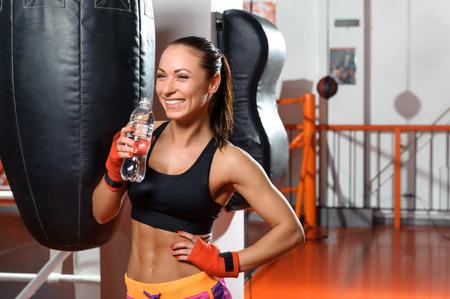 patada: Saludable y en forma. Mujer alegre joven de agua potable en un gimnasio de boxeo y contagiosa risa