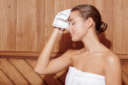 Sweating in sauna. Young woman feels the heat in sauna room and cleans sweat from her face with small white towel