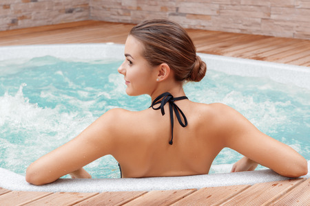 woman in spa: Beautiful spa. Back view of a young woman enjoying Jacuzzi in a spa center Stock Photo