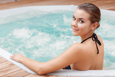 bathtubs: Beautiful spa. Back view of a young woman enjoying Jacuzzi in a spa center Stock Photo