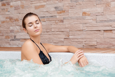 whirlpool: Absolute aqua magic. Young woman in swimming suit closes her eyes bathing in a whirlpool in a spa center