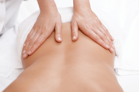 Nessun dolore solo piacere. Close-up del massaggiatore femminile mani dando massaggio alla schiena per una giovane donna