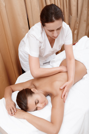 masseuse: Spa and wellness. Young woman relaxing on the belly and the masseuse massaged her back and shoulders Stock Photo