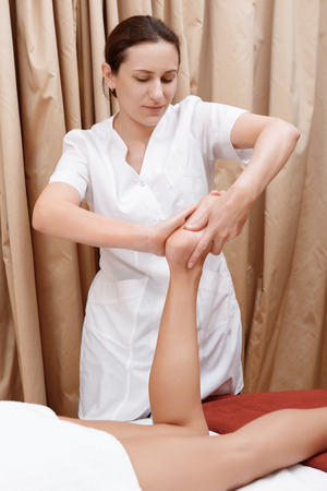 masseuse: Relief. Close-up of a masseuse massaging foot of a young woman
