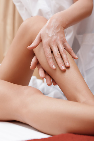 masseuse: Slim legs. Close-up of a masseuse massaging legs of a young woman in spa center Stock Photo