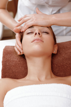 masseuse: Face lifting massage. Close-up of a masseuse hands massaging face of a young female client of a spa salon