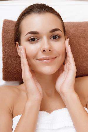 salon beaut�: La douceur divine. Close-up d'une jeune femme s�duisante palming joyeusement son visage avec un sourire au salon de beaut�