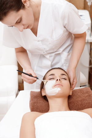 salon beaut�: Face � la nutrition de soins. Esth�ticienne application d'un masque avec une brosse sur un visage de femme dans un salon de beaut�