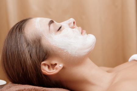 beauty parlor: Close-up of a young brunette peacefully relaxing with a beauty mask on her face in a beauty parlor