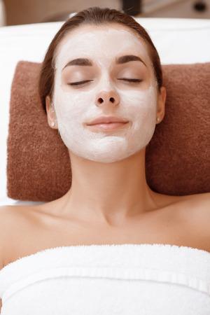 salon beaut�: Close-up d'une jeune femme brune de d�tente pacifiquement avec un masque de beaut� sur son visage dans un salon de beaut�