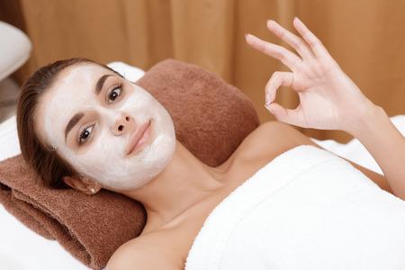salon beaut�: Service de la beaut� parfaite. Jeune femme montrant ok lorsque la cam�ra se d�tendre dans un salon de beaut� avec un masque blanc sur le visage