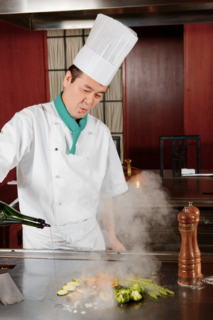 Spice cuisine. Japanese cook in uniform pouring sauce on fried vegetables on hot oven photo