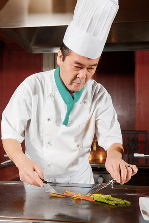 High cuisine. Japanese cook making a dish out of fried mushrooms, broccoli, asparagus, sweet pepper and zucchini and puts it on a table photo