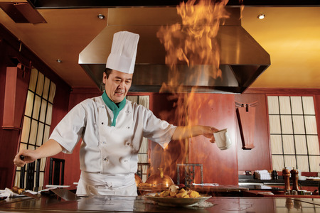 Kitchen hell. Japanese cook frying a vegetarian meal in burning flame of spirit on restaurant kitchen Banque d'images