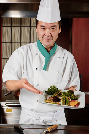 Light healthy meal. Smiling Japanese cook presents his meal of fried vegetables photo