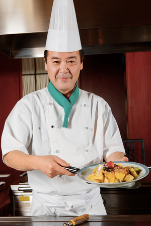 Special dessert. Japanese cook demonstrating his sweet fruit dessert and smiles to the camera photo