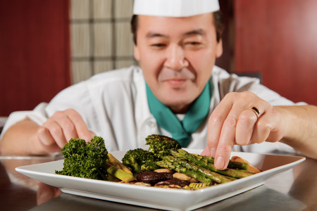 Asian vegetables. Close-up of fried asparagus, mushrooms and broccoli arranged in a plate by a cook in blurry Imagens