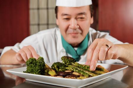 brocoli: Vegetales orientales. Primer plano de espárragos fritos, champiñones y brócoli dispuestos en una placa por un cocinero en borrosa Foto de archivo