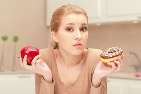 hesitating: Being in doubt. Nice young blonde woman in her kitchen sits holding apple in one hand and donut in another hand hesitating and trying to choose what she has to eat