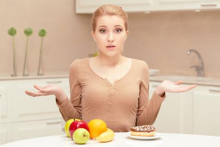 dudando: Difícil elección. Mujer bonita joven que se sienta confundido y dudando entre la fruta y la placa con el buñuelo en su mesa tratando de elegir alimentos adecuados Foto de archivo