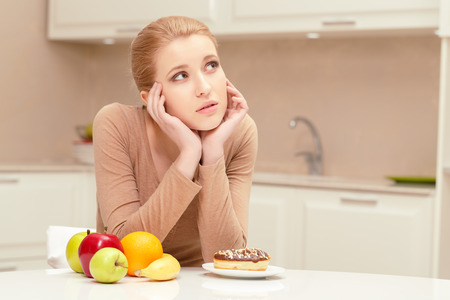 the right choice: Thinking about right choice. Pretty lady confused and sad about making a choice between fruit and sweet donut sitting in her kitchen at the table
