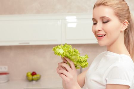 Exciting and useful. Young blonde lady in the kitchen feeling happy, holding lettuce leafs in her hands and smiling Stock Photo