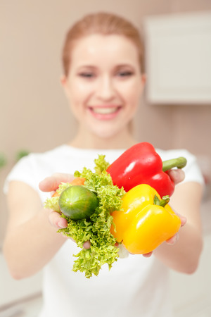 broadly: Tasty offer. Young beautiful woman gives you lettuce pepper and cucumber smiling broadly